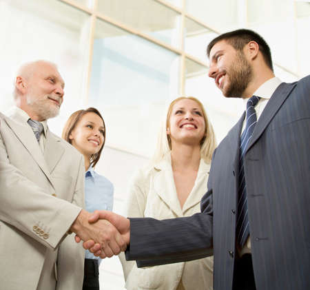 Business people shaking hands in front of a modern office centre photo