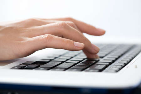 paypal: Female fingers typing a business document on the laptop