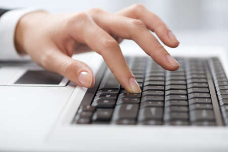 Close-up of female fingers typing a business document on the laptop  photo