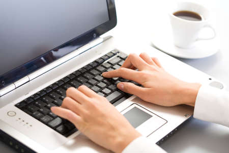 Close-up of hand touching computer keys during work photo