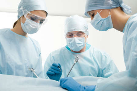 surgeon: Group of surgeons during their work