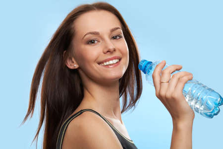 Beautiful girl drinking water from bottle on blue background photo