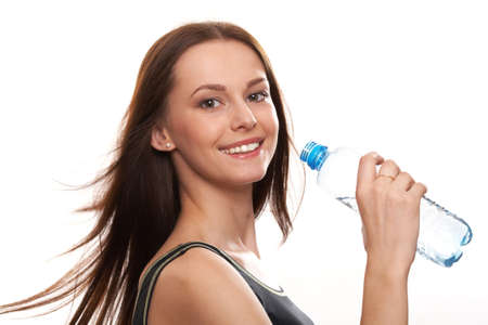 girl drinking water: Beautiful girl drinking water from blue bottle on blue background