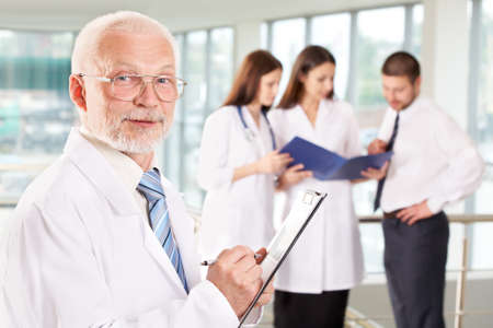 A portrait of doctor with two attractive nurses and patient in the background Stock Photo - 9372635
