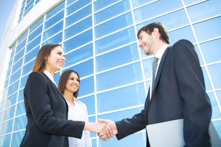 Young and successful businesspeople shake hands against the modern office building photo