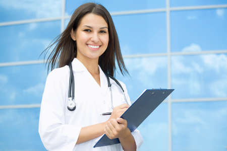 Young female doctor stand against a hospital building photo