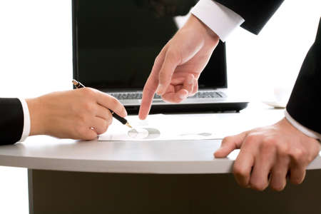 Close-up of business partners hands over papers discussing them   photo
