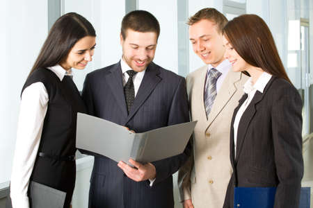 Group of young business people discuss the document in an office corridor  photo