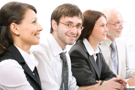 Face of businessman looking at camera with smile between his colleagues photo