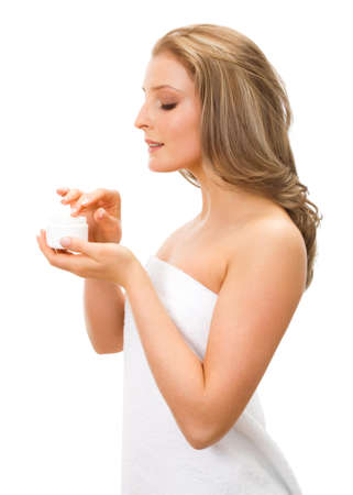 moisturiser: Young adult girl applying moisturiser cream. Stock Photo