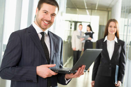 Happy young businessman using laptop in business building,  photo