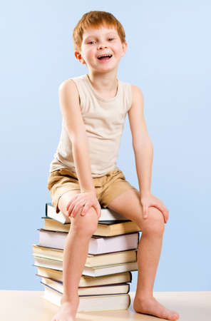 Image of happy schoolboy sitting on the heap of books  photo