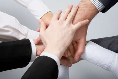 work together: Handen op de top van elkaar. Symbolische foto.