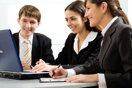 Group of business people working on laptop with their manager at the office photo