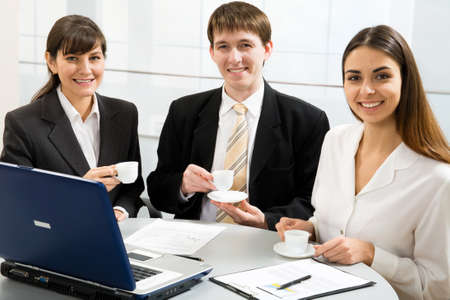 Three smiling attractive young business people on coffe break photo