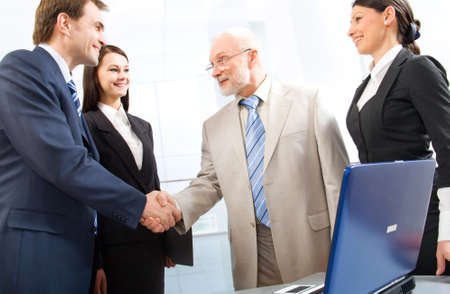 civility: Group of four business people shaking hands in an office Stock Photo