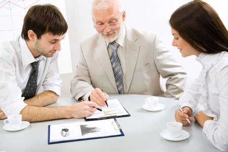 Portrait of business people sitting around table and looking at document