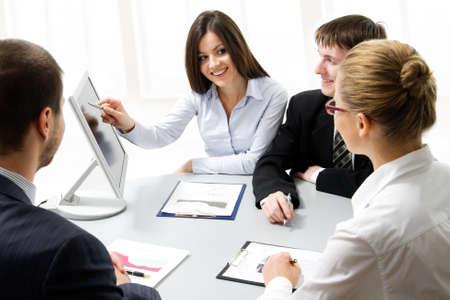 Boardroom meeting: Business people looking at monitir, talking at meeting table in office