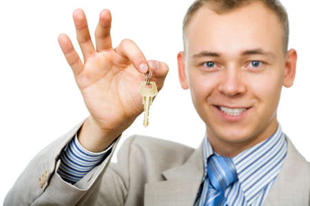 Young business man holding keys in his hand, white background photo