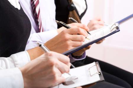 cuadro sinoptico: Fila de las manos tomando notas durante un seminario