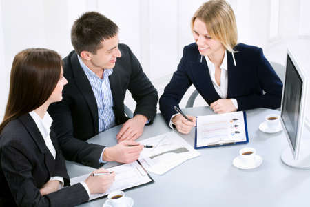 Successful businessman and his pretty colleagues working at office Stock Photo - 10492852