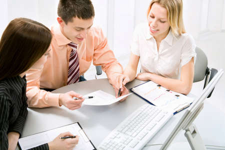 financial guidance: Successful businessman and his pretty colleagues working at office Stock Photo