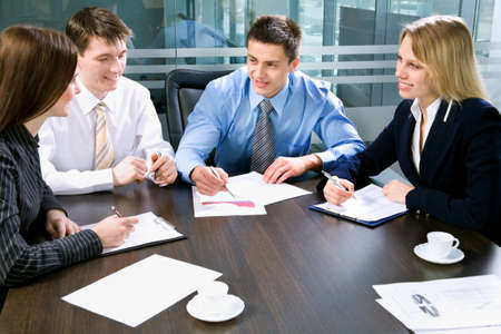 financial agreement: Image of four business people working at meeting Stock Photo