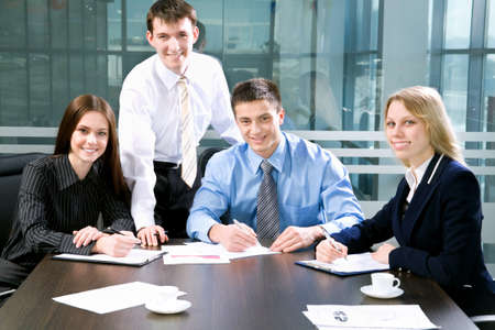 businessmeeting: Four business colleagues sitting around table and working together, looking at camera, smiling
