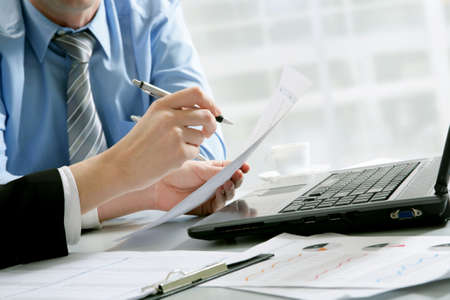 executive courses: Close-up of business partners hands over papers discussing them Stock Photo