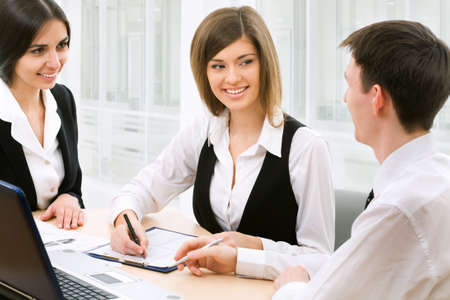 financial guidance: Image of three business people working at meeting