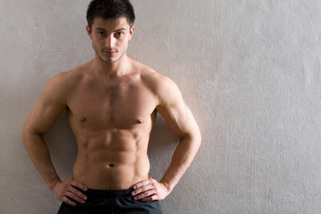 Portrait of muscular man leaning against the wall   photo