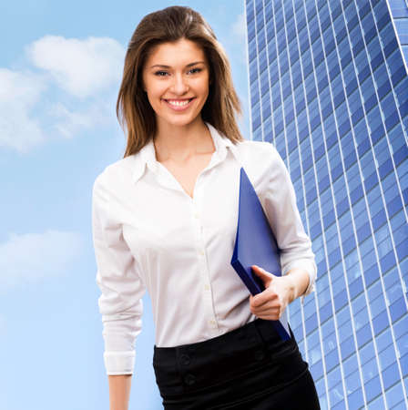 sexy business woman: Beautiful business woman on the background of the modern office and the blue sky