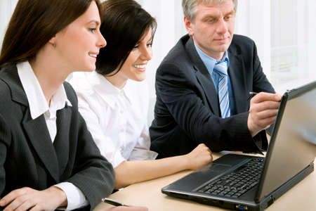 Three business colleagues sitting around table and working together, looking at monitor Stock Photo - 10539452