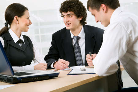 financial planner: Business people at the office with a laptop