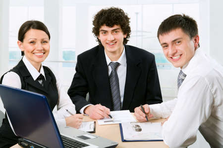 legal advice: Three business colleagues sitting around table and working together, looking at camera