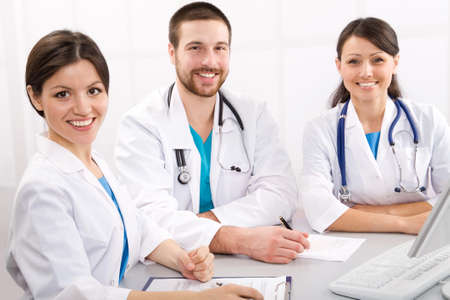 white coats: Smiling medical doctors on a workplace Stock Photo