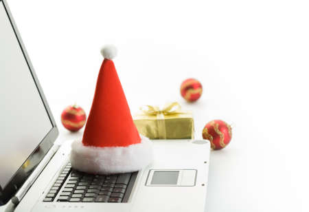 Santa Claus hat and christmas gifts on a workplace photo