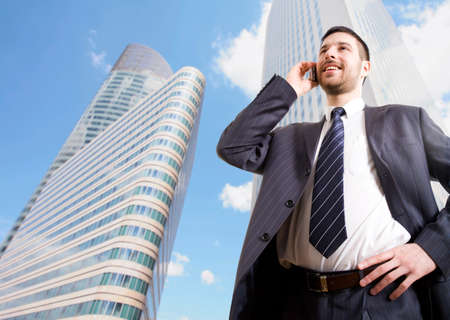 Businessman with cellphone on a background of skyscrapers photo