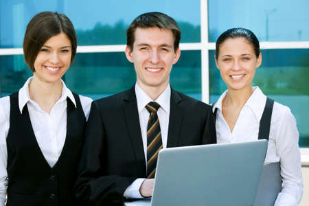 Young business people working against modern office building photo