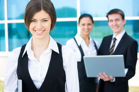 foreground: Beautiful woman on the background of business people