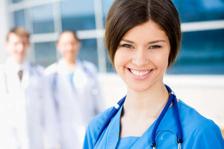 female doctor: Young female doctor stand against a hospital building