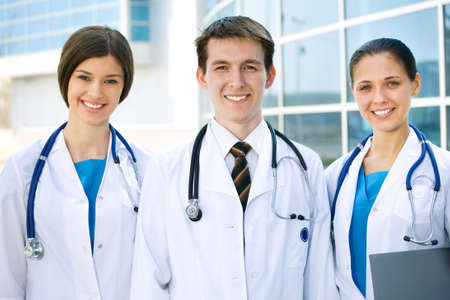 Young doctors are standing outside the hospital and looking at camera photo