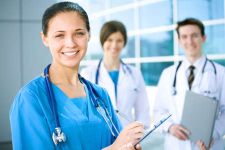 Portrait of a female doctor with two of her co-workers against modern hospital building Stock Photo - 11010583