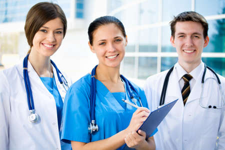 Young doctors standing against a hospital building photo