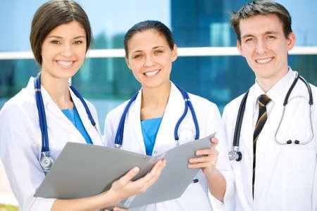 grupo de doctores: Los m�dicos j�venes est�n de pie fuera del hospital y mirando a la c�mara