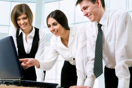 office environment: Happy young business people working together in a modern office building