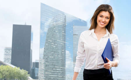 sexy secretary: Beautiful young businesswoman among the skyscrapers of the modern business center Stock Photo