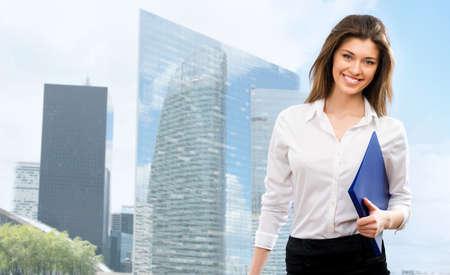 Schöne junge Geschäftsfrau zwischen den Wolkenkratzern der modernen Business-Center