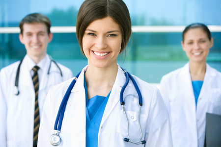 Portrait of a beautyful young female doctor standing in front of his team and smiling photo