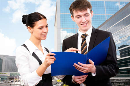 good looking: Young business colleagues working together on background a modern office building